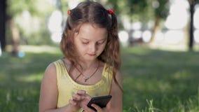 Een meisje zit op gras in een park op een zonnige de zomerdag en communiceert met vrienden in sociale netwerken gebruikend een sm