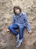 Een meisje zit op het zand Stock Afbeelding