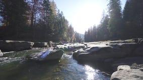 Een meisje zit op een rots in het midden van de rivier stock videobeelden
