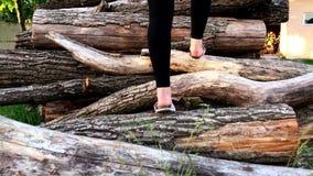 Een meisje in zwarte broek loopt op groen gras en beklimt op logboeken die op de grond liggen Achter mening stock video