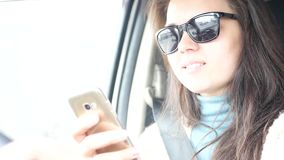 Een meisje in zwarte glazen, die de auto bekijken terwijl het drijven, glimlacht 4K 30FPS 3840x2160 stock video