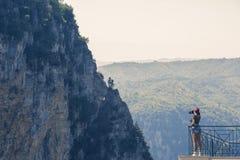 Een meisjesfotograaf in een rood GLB met een camera bevindt zich op het balkon tegenover de kloof van Vikos in Griekenland Vikosk Stock Fotografie