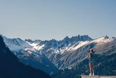 Een meisjesfotograaf in een rood GLB met een camera bevindt zich op het balkon tegenover sneeuw Zwitsers Alpen en bos van nationa Stock Afbeelding