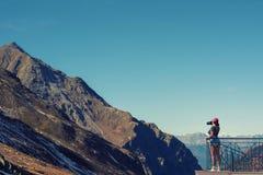 Een meisjesfotograaf in een rood GLB met een camera bevindt zich op het balkon tegenover sneeuw Zwitsers Alpen en bos van nationa Royalty-vrije Stock Afbeeldingen
