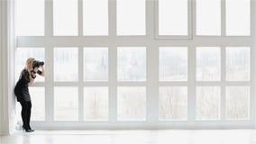 Een meisjesfotograaf tegen het grote venster stock video