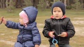 Een meisjesgeeuwen Zij houdt een haarspeld in haar handen Een jongen richt zijn vinger op iets stock video