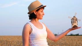 Een meisjeslandbouwer houdt een windmolenstuk speelgoed in haar hand tegen de achtergrond van een tarwegebied stock video