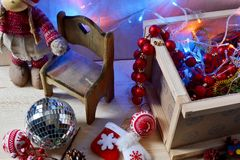 Een meisjespop in een de winterkostuum en een doos van Kerstmisdecoratie Stock Foto