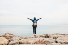 Een meisjesreiziger in een hoed met een rugzak naast het overzees heft omhoog haar handen op Reis, rust, wandeling, vrijheid royalty-vrije stock fotografie