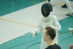 Een meisjesschermer die het schermen duel op toernooien hebben Het dragen van een kostuum en een helm stock fotografie