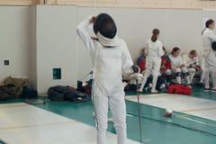 Een meisjesschermer die het schermen duel op toernooien hebben Een meisje die houdend een sabel bevinden zich stock foto
