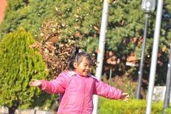 Een meisjesspel met droge bladeren Stock Afbeeldingen