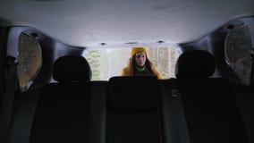 Een meisjestoerist neemt haar rugzak van de boomstam van een auto stock videobeelden