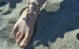 Een meisjesvoet met een shell halsband Royalty-vrije Stock Foto's