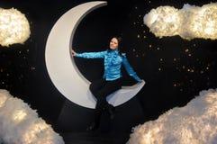 Een meisjeszitting op de maan en de wolken Stock Foto's