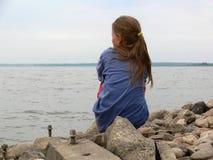 Een meisjeszitting op de rotsen door het strand stock fotografie