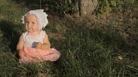 Een meisjeszitting op het gras in een witte en roze kleding en een bonnet, die haar mond openen het wrijven haar neus met vingers stock footage