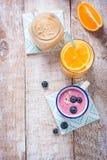 Een mengeling van drie smoothies met bosbes, sinaasappel en perzik op een houten achtergrond met exemplaarruimte Royalty-vrije Stock Afbeeldingen