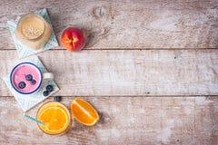 Een mengeling van drie smoothies met bosbes, sinaasappel en perzik op een houten achtergrond met exemplaarruimte Stock Fotografie
