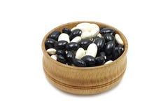 Een mengsel van korrels van zwart-witte bonen in een houten kom Stock Foto's