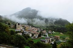 Een mening bij een klein Italiaans dorp met wolken en mist stock afbeelding
