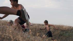 Een mening die van lopende kinderen, op een opleiding op een gebied concurreren stock video