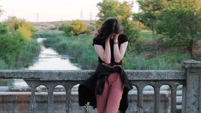 Een mening die van rechts naar links van een droevige vrouw, zich op een brug bevinden, die droevig haar gezicht met handen behan stock videobeelden