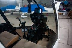 Een mening door de cabine van een kleine helikopter aan de behandelde sportenvliegtuigen in de hangaar Royalty-vrije Stock Fotografie