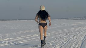 Een mening over een slanke vrouw in een bikini die in de winter lopen stock footage