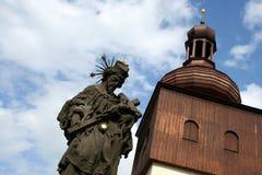 Een mening over zandsteen godsdienstig standbeeld en houten kerktoren Royalty-vrije Stock Afbeelding