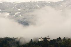 Een mening van Ambras-Kasteel in Innsbruck, Oostenrijk door bomen en tegen de achtergrond van bergen wordt omringd die royalty-vrije stock foto's