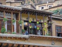 Een mening van een blokhuis in de historische stad van Masouleh, Geraniumbloemen schikte in Portiek van huis, Iran, Gilan stock foto's