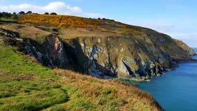 Een mening van de klippen door het overzees met witte wolken op de achtergrond Stock Foto's