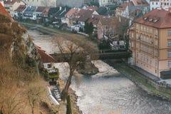 Een mening van de lucht aan mooie authentieke huizen en straten met een binnen rivier en een brug in de stad van Cesky Krumlov Stock Afbeelding
