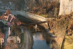 Een mening van de lucht aan mooie authentieke huizen en straten met een binnen rivier en een brug in de stad van Cesky Krumlov Stock Foto