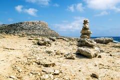 Een mening van de piramide van stenen op de rotsen van Kaap Greco CYP Royalty-vrije Stock Fotografie