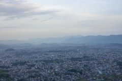 Een mening van de reusachtige stadsvallei op de achtergrond van het silhouet van de bergen in de avond onder zware hemel stock foto's