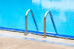 Een mening van een licht duidelijk blauw zwembad met staalladder Royalty-vrije Stock Foto's