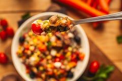 Een mening van een gespelde schotel op houten achtergrond met sommige ingredi?nten rond: wortelen, peper, tomaten, peterselie en  royalty-vrije stock afbeelding