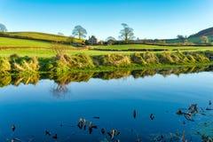 Een mening van het kanaal van Lancaster met een landbouwbedrijfhuis, door twee bomen wordt gegrenst die Stock Afbeelding