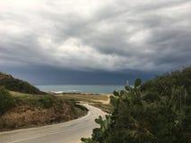 Een mening van het overzees en de weg in de voorgrond vóór het onweer met donkere grijze wolken die het eiland naderen stock foto's