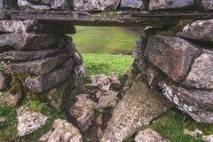 Een mening van het Piekdistrict door een gat in een muur maakte van rotsen en stenen royalty-vrije stock fotografie