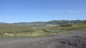 Een mening van het Targyn-dorp in Oostelijk Kazachstan en auto's op de weg Bergen van Oostelijk Kazachstan stock footage