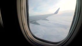 Een mening van het venster van een passagiersvliegtuig die laag over de wolken in slecht weer vliegen stock video