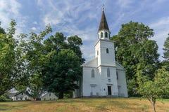 Een mening van een houten witte die kerk door bomen wordt omringd royalty-vrije stock foto