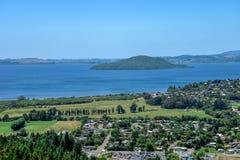 Een mening van Meer Rotorua met eiland en een stad Stock Afbeeldingen