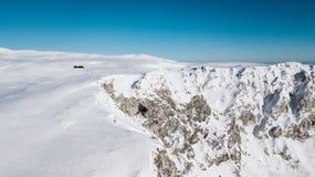 Een mening vanaf de bovenkant van de berg aan de klippen die met sneeuw op een zonnige dag worden behandeld stock afbeelding