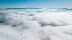 Een mening vanaf de bovenkant van de berg aan de vallei die met wolken met een duidelijke blauwe hemel op een zonnige dag wordt b stock foto's