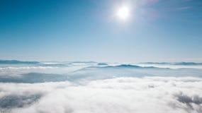 Een mening vanaf de bovenkant van de berg aan de vallei die met wolken met een duidelijke blauwe hemel op een zonnige dag wordt b royalty-vrije stock afbeeldingen
