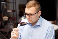 Een mens aan alcohol wordt gewijd drinkt wijn die stock afbeelding